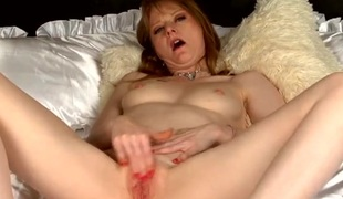 Redheaded mom masturbates on white satin bath linens